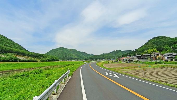 田舎道の風景。道路の右側には農地が、左側には川が、むこうには山が見える。