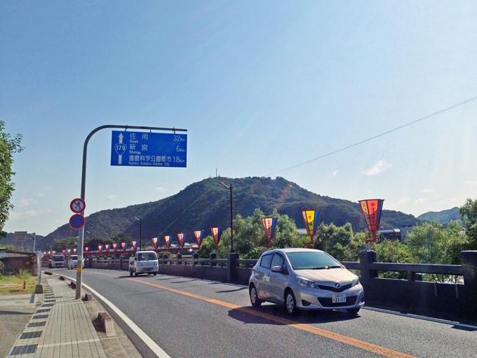 片側1車線の対面通行の道路。道路上に吊るされた青い案内標識には、「国道179号線」のマークや、「佐用町まで32km」などのこの先の地域への距離の目安が表示されている。