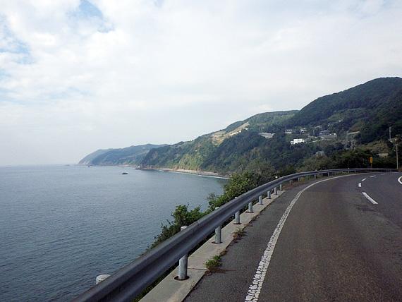 山道の写真。カーブの外側が断崖絶壁になっていて、その先に海が見える。