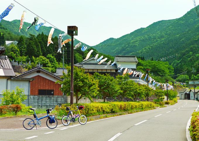 兵庫県神崎郡神河町にある「グリーンエコー笠形」に続く道路に沿って、たくさんの「鯉のぼり」が道しるべとして吊るされている風景。ずっと先まで鯉のぼりの列が続いている。道路には2台の自転車、「ニューワールドツーリスト」と「コメットR」が停められている。