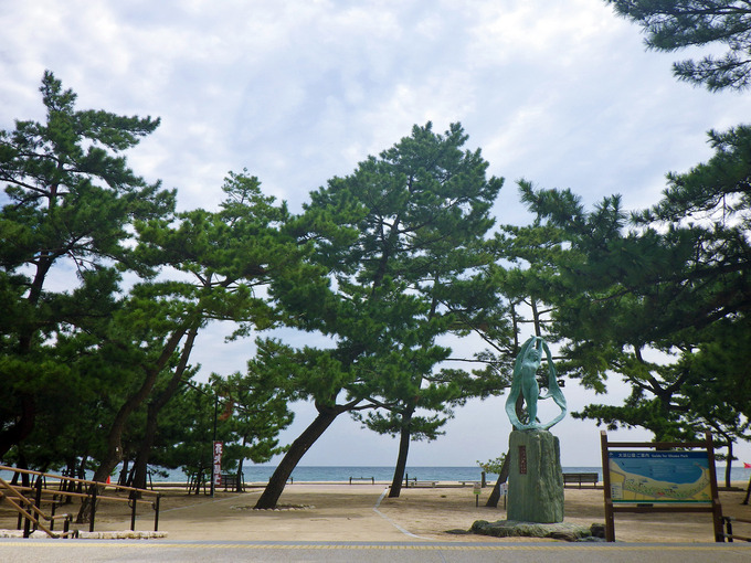 淡路島の「大浜海水浴場」付近の写真。たくさんの松の木があり、その向こうに砂浜と海が見える。松の木の下に、人の形をした青銅色の銅像が建てられている。