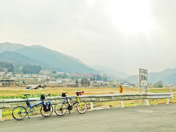京都・大原の中心付近で大原の風景を見渡した写真。山に囲まれた土地に農地や家が見える。手前には2台の自転車、「ニューワールドツーリスト」と「コメットR」が停められている。