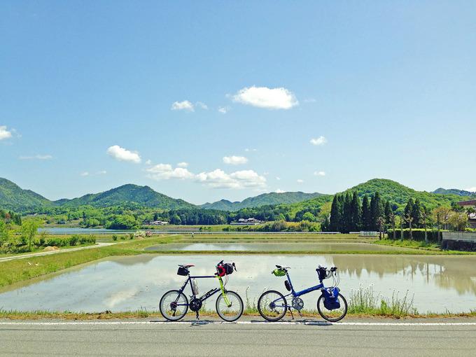 三田の田園風景の写真。田植え前の水が張られた田んぼに空や雲が映っている。むこうには緑色の山々が見える。手前には2台の自転車、ニューワールドツーリストとコメットRが停められている。