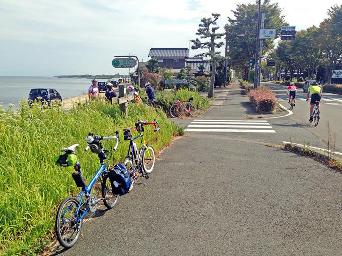 滋賀県高島市新旭の「木津」交差点付近から見る琵琶湖の風景。緑色の草むらのむこうに、青い琵琶湖の水面が広がっている。近くの道路脇には、自転車を置いて休憩しているサイクリンググループや、走ってゆくロードバイクの姿がある。