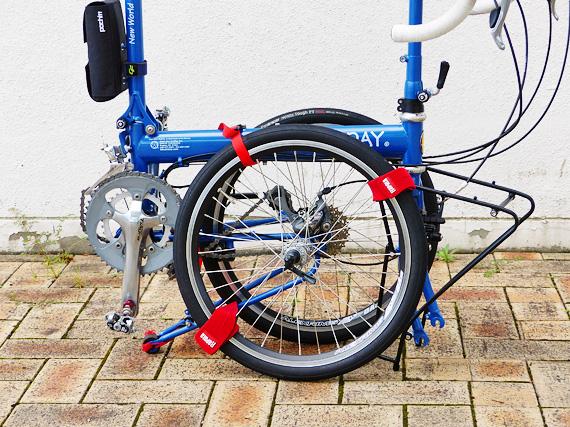 バイクフライデーの折り畳みミニベロ「ニューワールドツーリスト」が折りたたまれている写真で、赤いベルトが3箇所に装着されている。