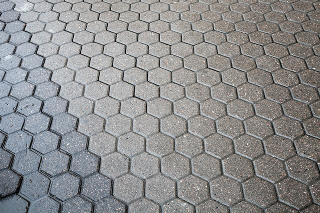 アスファルトでない路面の一例として、コンクリートで造られた路面の写真。表面が濡れていて滑りやすそうなのが判る。