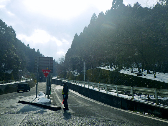 滋賀県大津市内の国道367号線の「途中越」付近の道路の写真。旧道から国道に合流する交差点になっている。周囲には背の高い木々が立ち並び、地面には雪が積もっている。