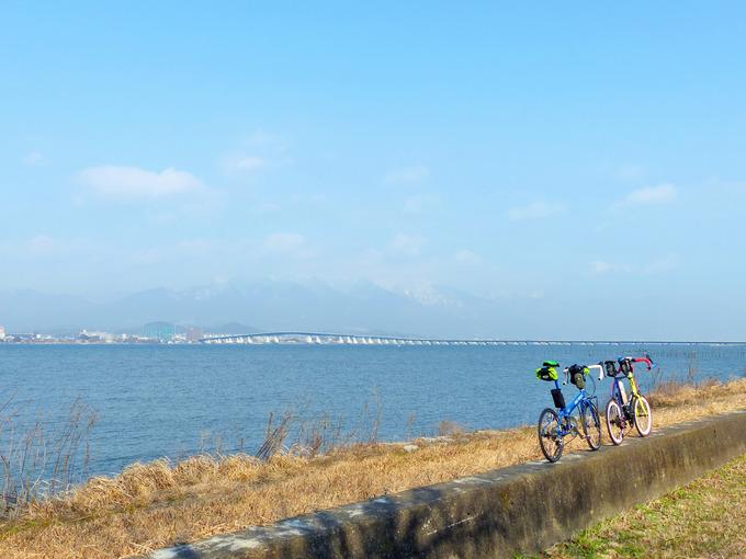 青い琵琶湖の水が広がる風景のむこうに、琵琶湖大橋が見える。はるか遠くには冠雪した比良山系の山々が見える手前には2台の自転車、「ニューワールドツーリスト」と「コメットR」が停められている。