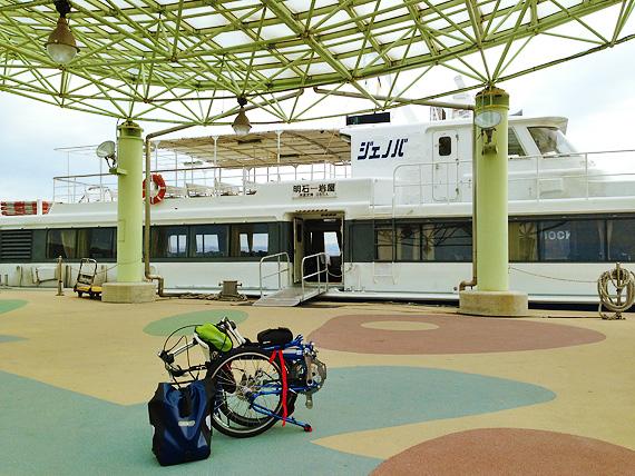 淡路島「岩屋港」の桟橋の風景。桟橋に到着した明石と淡路島・岩屋を結ぶ高速船「淡路ジェノバライン」の船が写っている。船の降り口の先には、バイクフライデーの折り畳み小径車「ニューワールドツーリスト」が折り畳まれた状態で置かれている。
