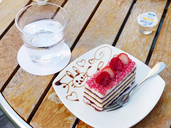 筆者が注文したケーキの写真。ベリーのソースとスポンジとクリームが何層にも重ねられたケーキで、上にはラズベリーと苺が乗っている。白いお皿にはチョコレートで可愛い絵が描かれている。