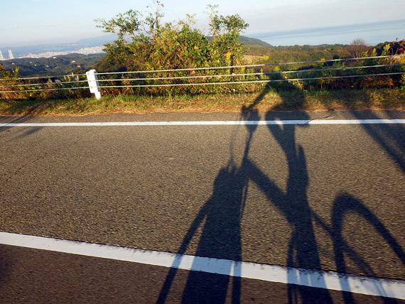 夕陽が当たる道路に、自転車に乗った筆者の影が映っている写真。