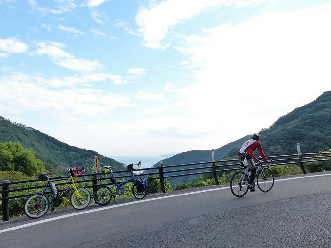 淡路島・由良の山道の風景の写真。坂道のガードレールのむこうに山の稜線と海が見える。ガードレールの前には2台の自転車、バイクフライデーの折り畳みミニベロ「ニューワールドツーリスト」とミニベロロード「コメットR」が停められている。その前を1台のロードバイクが坂を登ってゆく。