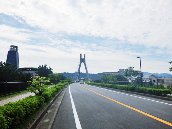 淡路島の洲本市内にある「州浜橋」と道路の写真。州浜橋は鉄筋コンクリートとワイヤーで造られた吊り橋である。