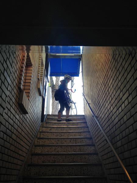 地上と地下を結ぶ階段を地下側から見上げた写真。地上側から入ってくる光は明るく眩しい。そこに自転車を手に抱えて階段を降りてくる友人の姿。