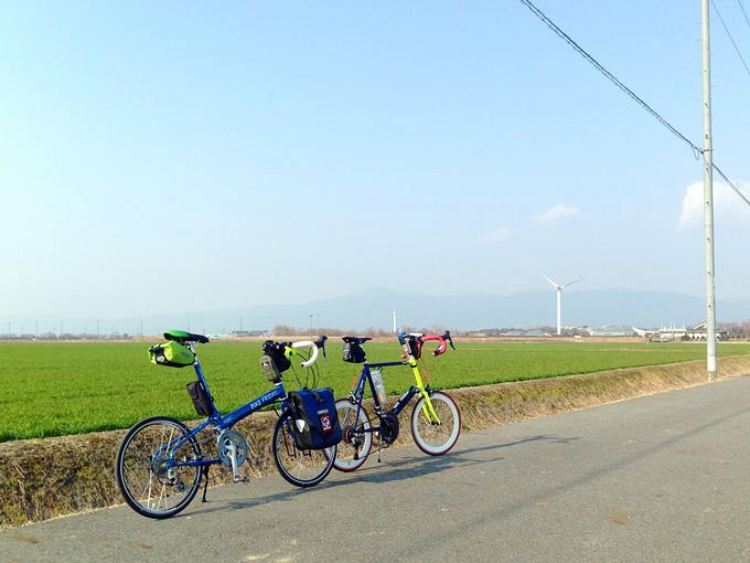 滋賀県守山市内の農地が広がる風景。緑色の作物が植えられている。むこうには風力発電の風車が見える。手前には2台の自転車、「ニューワールドツーリスト」と「コメットR」が停められている。
