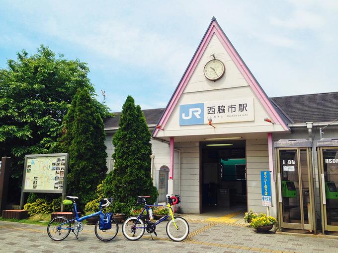JR「西脇市駅」の駅舎の写真。入り口は三角屋根になっている。駅の前には、2台の自転車「ニューワールドツーリスト」と「コメットR」が停められている。