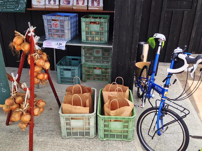 黒く塗られた木製の建物の前に、カゴに入れられた玉ねぎや、紐で吊るされた玉ねぎがたくさんある。その横に青い自転車が停められている。
