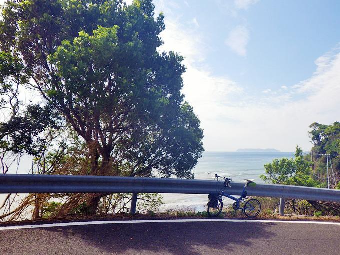 淡路島・洲本市南部の海岸付近の風景。ゆるやかな下り坂の途中にバイクフライデーの折り畳みミニベロ「ニューワールドツーリスト」が停められていて、その後ろには木々が立ち並び、木々の間から海が見え、海の向こうには離島「沼島」が見える。