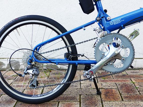 バイクフライデーの折り畳みミニベロ「ニューワールドツーリスト」の後ろ半分を真横から見た写真。細い青いパイプで作られた三角形のような形をした部分にギアやブレーキやタイヤなど色々な部品が装着されている。