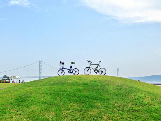 芝生が生え揃った緑色の小さな丸い丘の上に、青い自転車と緑色の自転車が停められている。その向こうには、遠くに明石海峡大橋が見える。