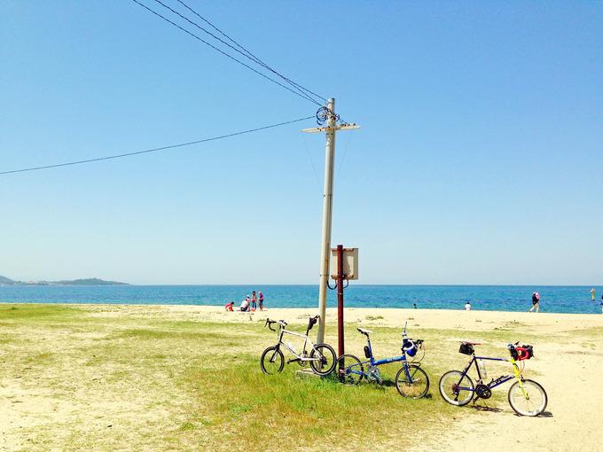 「慶野松原海水浴場」の写真。青い海・白い砂浜が広がる風景の真ん中に、3台のミニベロが停められている写真。