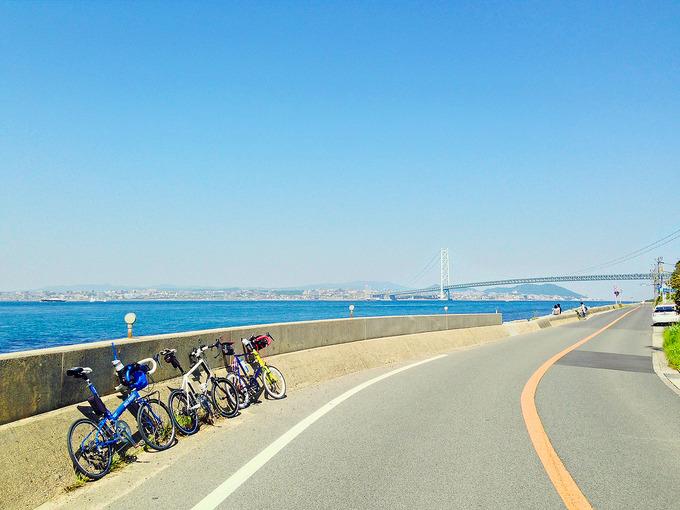 淡路島・松帆の浦付近の風景の写真。左側には青い海が広がり、前方には明石海峡大橋が見える。道路脇には3台のミニベロが停められている。