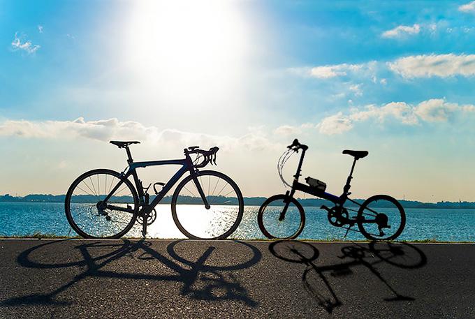 ミニベロ(小径車)とロードバイク、2種類のタイプの異なる自転車を並べた写真。青空と湖を背景に、2台の自転車のシルエットがくっきりと浮かび上がり、タイヤの大きさやフレームの形など、それぞれの違いが表れている。