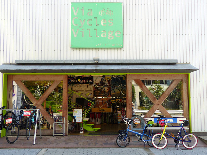 大阪にある自転車店「ヴィアサイクルズヴィレッジ」の店舗前の写真。倉庫のような建物で、お店の前にはバイクフライデーの折り畳みミニベロ「ニューワールドツーリスト」と友人の自転車「コメットR」が停められている。