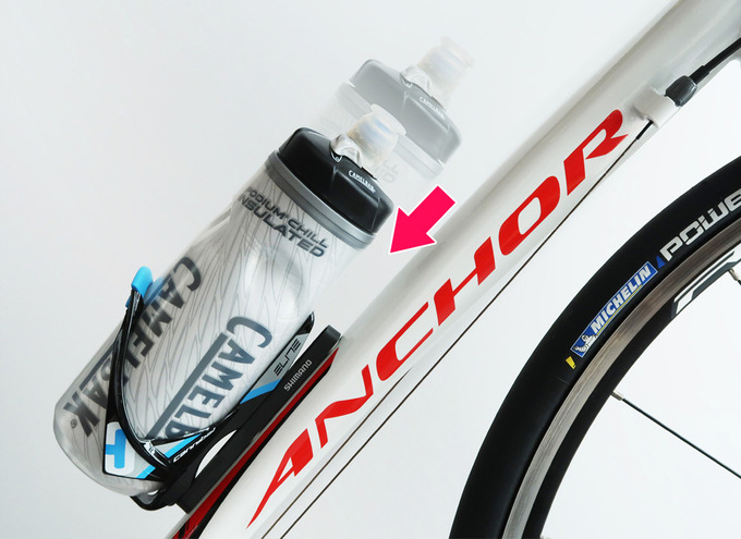 ロードバイクのボトルケージの取り付け位置をズラして調整する様子のイメージ写真